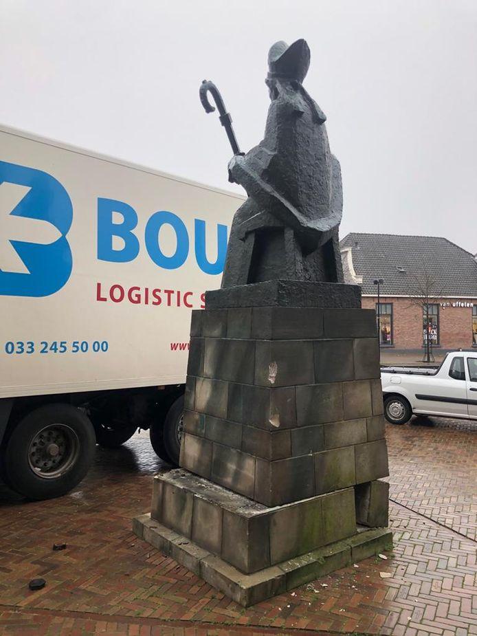 Een vrachtwagen is tegen het beeld van Plechelmus aangereden waardoor het object nu scheef op de sokkel staat.