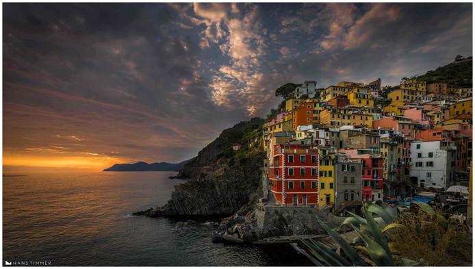 Het is een veelvuldig gefotografeerd punt in Nationaal Park Cinque Terre in Italië. Dit keer worden de huizen van Riomaggiore, een van de vijf dorpen in het nationaal park, belicht door een mooie zonsondergang.