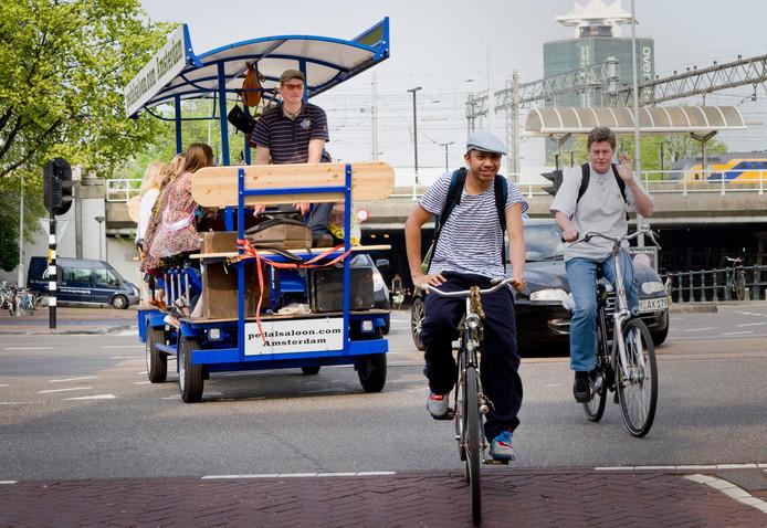 Buitelandse toeristen op een bierfiets door Amsterdam. Een beeld waarvan Ko Koens denkt dat Breda er niet echt op zit te wachten.