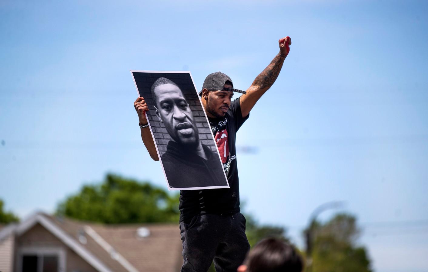 Een man houdt een foto omhoog van de omgekomen George Floyd.