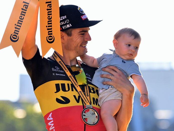 Wout van Aert op het podium in Parijs, met zijn zoontje Georges die in januari werd geboren. Om 23.30 uur vliegt Van Aert alweer naar Japan voor de Olympische Spelen.