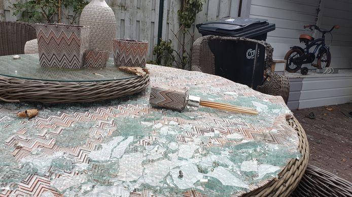 De versplinterde glasplaat van de tuintafel met daarachter de opgeblazen stoel. Allemaal veroorzaakte door zwaar vuurwerk dat over de schutting werd gegooid in de Eindhovense wijk Vaartbroek.