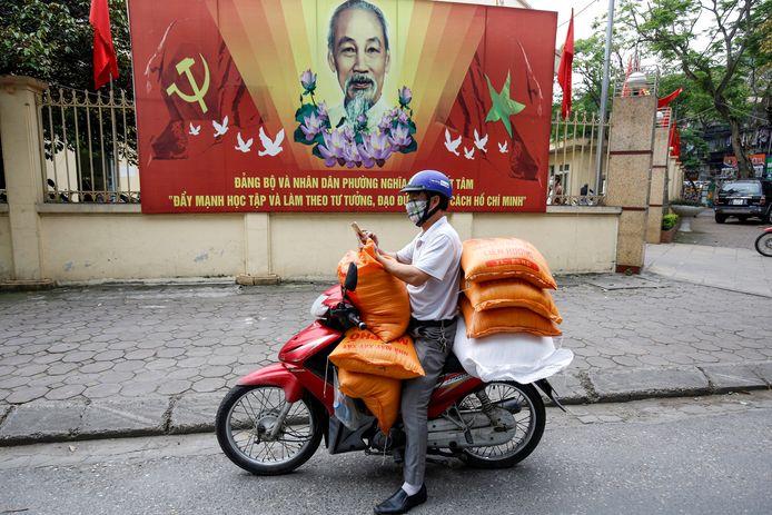 Archiefbeeld van een man de rijstzakken ronddraagt om te verdelen aan de arme mensen tijdens de coronacrisis in Hanoi, Vietnam.
