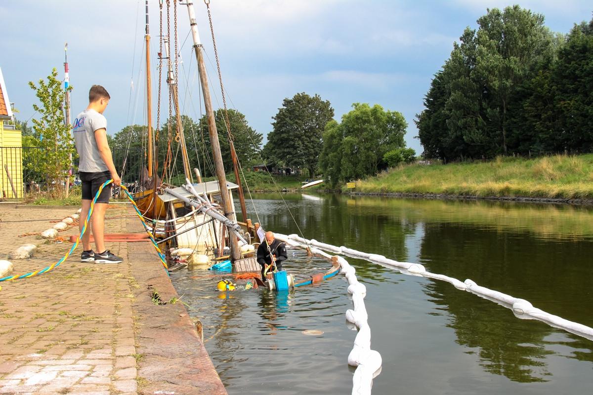 Medewerkers van duikbedrijf DCN aan het werk aan de kotter, die grotendeels onder water verdwenen is.
