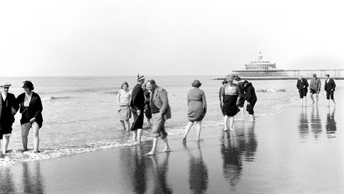 1937. Rokken omhoog en de branding in van het Scheveningse strand.