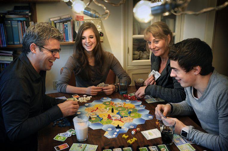 Een gezin speelt Kolonisten van Catan. Beeld Marcel van den Bergh / de Volkskrant