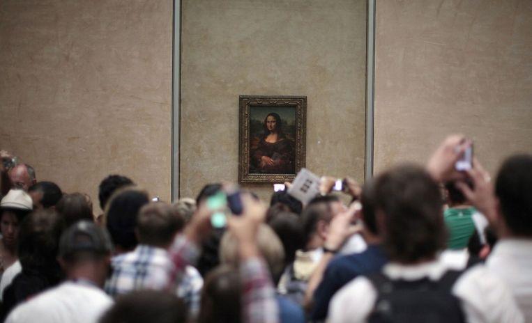 Toeristen verdringen zich rond de Mona Lisa in het Louvre in Parijs. Beeld REUTERS
