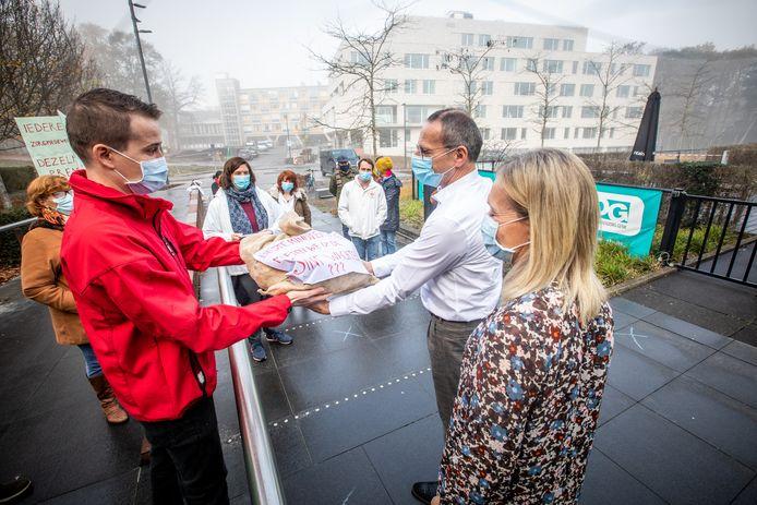 Het zorgpersoneel uit ziekenhuizen en andere sectoren geeft 985 chocolademuntjes aan het Woonzorgcentrum Toermalien als symbool tijdens de protestactie.