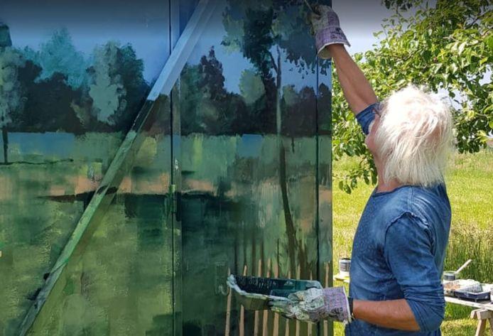 Kunstenaar Jan Aanstoot bezig met het beschilderen van de schaftkeet in de Generatietuin. Deze week maakt hij de klus af, zodat alles klaar is voor de kunstmarkt.