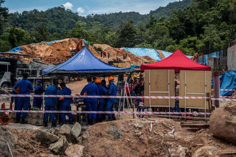 Maleisische reddingswerkers zoeken naar vermisten onder het puin. Beeld AFP