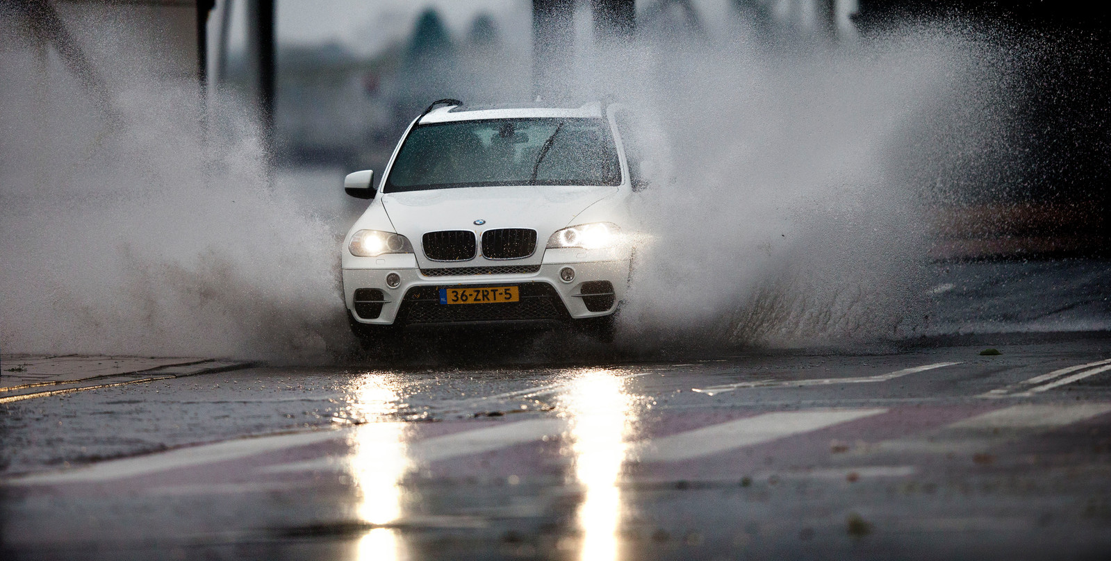 Een auto rijdt door enorme plassen in Rotterdam. In het hele land wordt er regen verwacht.