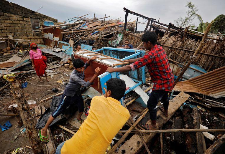 Bewoners in de West-Indiase deelstaat Gujarat bergen hun eigendommen nadat de cycloon Tauktae in hun dorp huisgehouden heeft. Beeld REUTERS