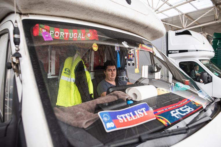 Een Reomeense vrachtwagen chauffeur wacht de controle van zijn wagen af. Beeld Bart Koetsier