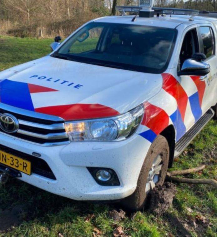 Een nieuwe politieauto van Hof van Twente kwam zondag vast te zitten in de modder. Een boer schoot te hulp.