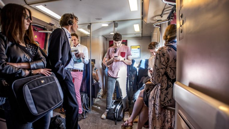 Reizigers moeten vanwege te weinig zitplekken staan tijdens hun reis. Beeld Raymond Rutting/de Volkskrant