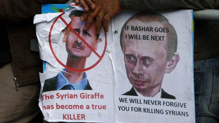 Syrische demonstrant houdt een protestbord vast met karikaturen van president Assad en Russisch premier Putin. Beeld reuters
