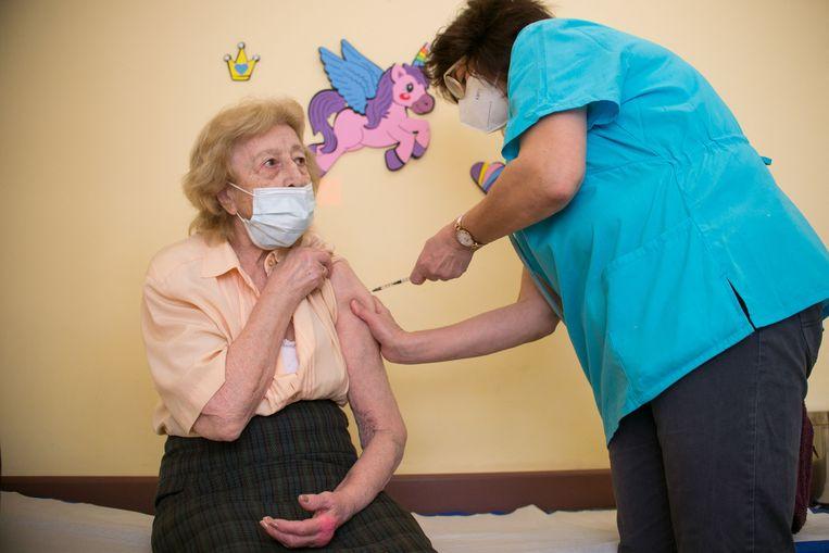 Een 91-jarige vrouw krijgt het AstraZeneca-vaccin toegediend in het Pirogov-ziekenhuis in de Bulgaarse hoofdstad Sofia. Beeld AFP
