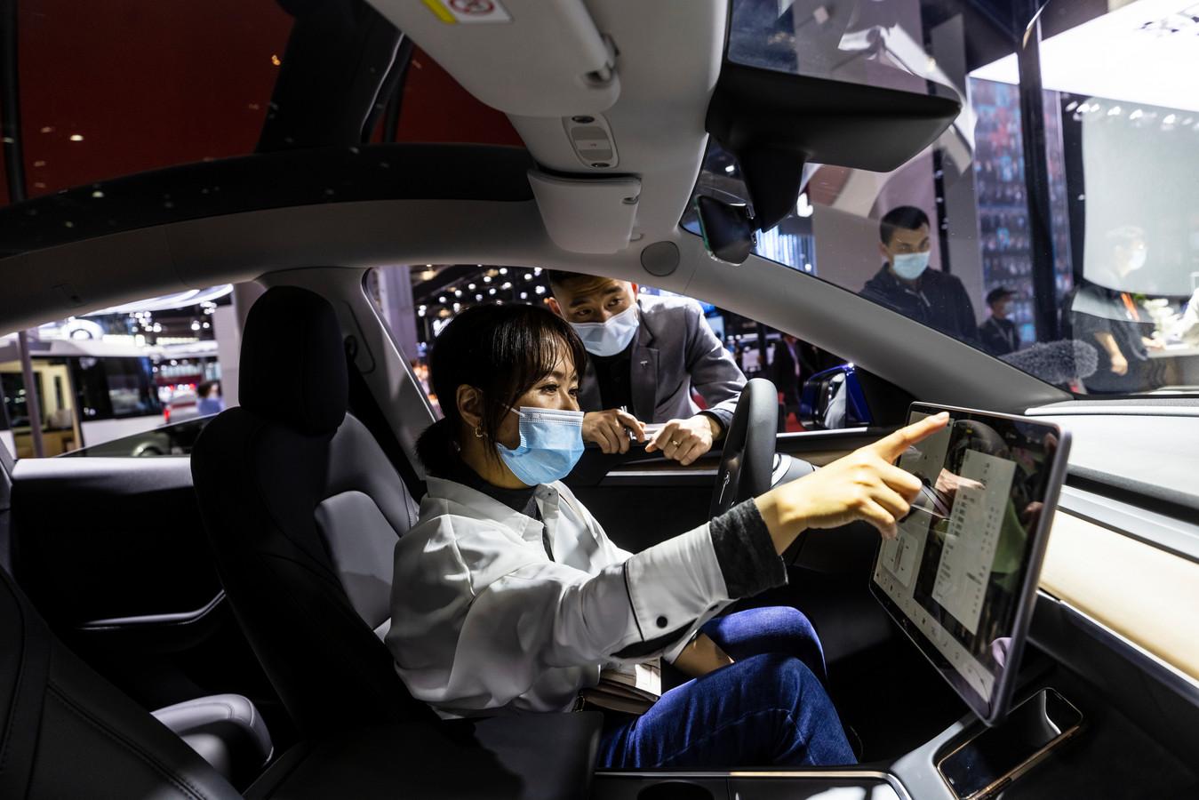 Een vrouw probeert het infotainment uit van een Tesla Model 3.