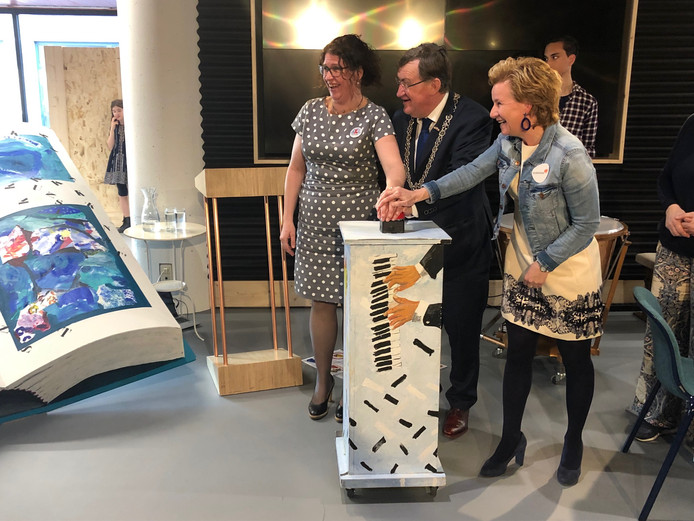 Samen drukken Janneke van Summeren (links), burgemeester Henk Hellegers en Gabri Raaijmakers op de knop waarna een papierfontein achter het boek begon te spuiten.