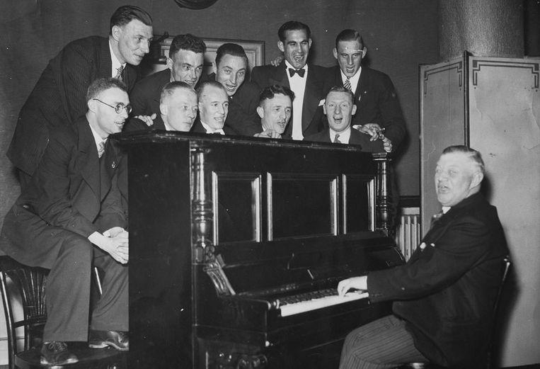 Voor zijn tachtigste verjaardag krijgt hij - hier achter de piano - een groot feest in het clubhuis van Ajax. De cadeaus: een televisie en veel sigaren Beeld Privécollectie Jack Reynolds