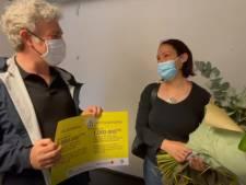Alain Maron remet des fleurs à la femme qui a reçu la millionième dose de vaccin à Bruxelles