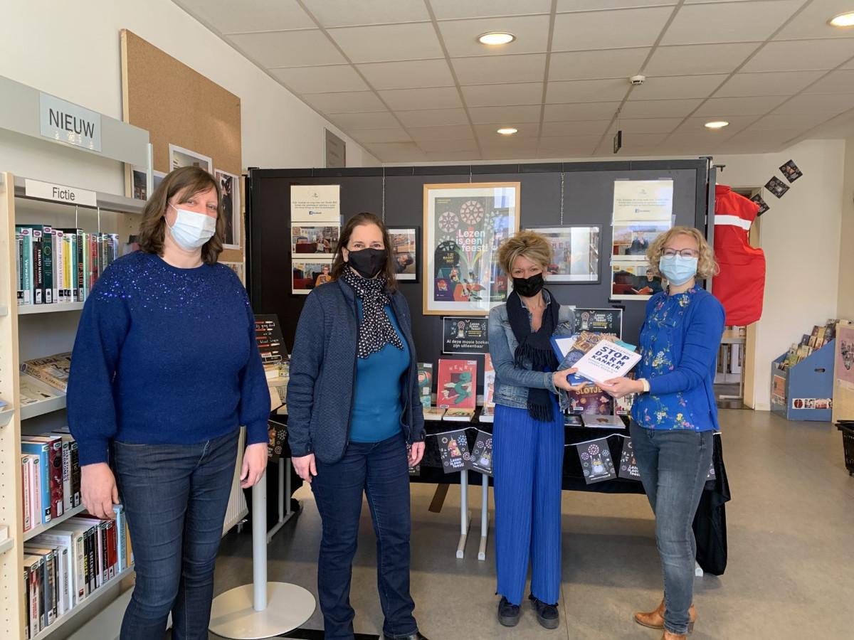 Van links naar rechts: bibliothecaris Katleen Van Eecke, schepen van Bibliotheek Elke Tweepenninckx (Groen) en Olen Tegen Kanker-leden Kim Ooms en Elke Tegenbos bij de overhandiging van de boeken.