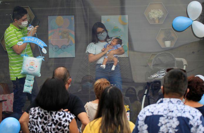 Een koppel laat in een speciale cabine trots hun pasgeboren kind zien aan familie en vrienden