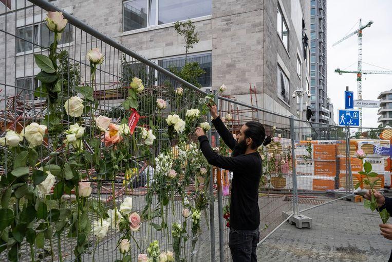 Er werden bloemen voor de slachtoffers aan het hek gehangen door collega's van de omgekomen bouwvakkers. Beeld Klaas De Scheirder