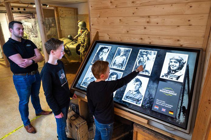 Robert Braam met twee scholieren bij de touchscreens met zeven hoofdpersonen in oorlogsmuseum Niemandsland. Kleinere versies komen in de voormalige legertruck.