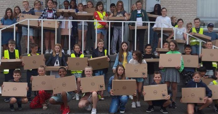 De laptops werden overhandigd aan de kinderen