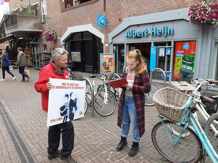 Krista van Velzen van de SP kijkt toe hoe Rosanna Melieste op de Eglantier in Apeldoorn haar krabbel zet.