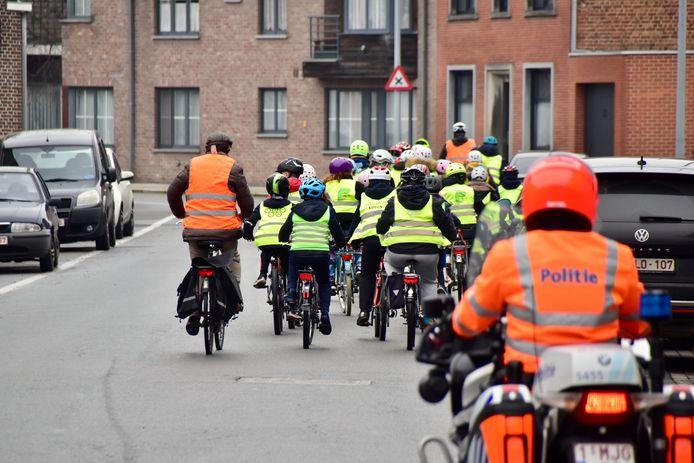 De leerlingen van het zesde leerjaar, onder leiding van meester Filip, trekken op pad om de fietszone in het centrum van Sint-Eloois-Winkel te verkennen. Een politieman vergezelt hen.