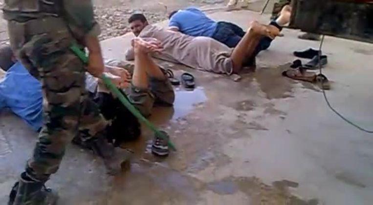 Syrische burgers worden mishandeld aan een checkpoint tussen de steden Salamiyah en Hama, september 2012. Beeld AFP