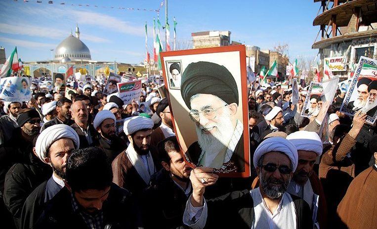 Aanhangers van de regering dragen portretten van ayatollah Khamenei en de in 1989 overleden ayatollah Khomeini. Beeld Reuters