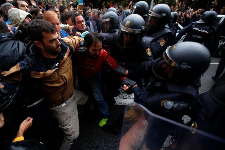 De Guardia Civil en Spaanse nationale politie in Barcelona gingen driest tekeer tegen de nochtans vreedzame kiezers.Er zouden in totaal meer dan 700 gewonden gevallen zijn, onder wie meerdere ernstig.  Beeld AP