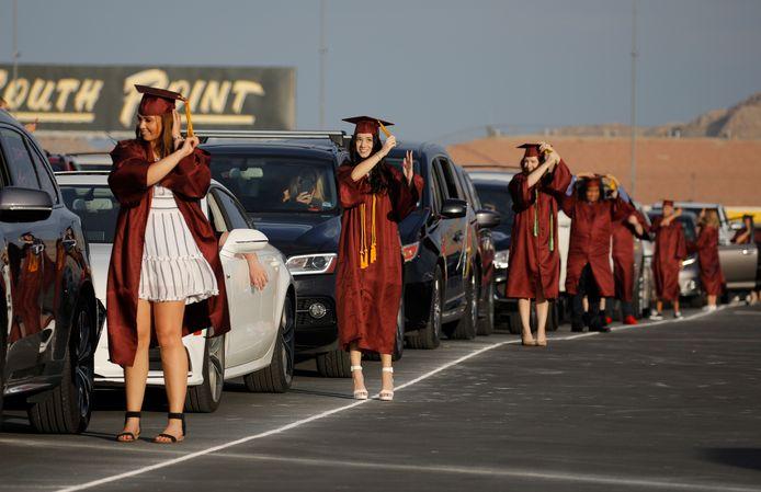 Scholen over de hele wereld moeten dit jaar creatief zijn om hun diploma-uitreikingen coronaproof te maken. Op de foto een drive-thru diploma-uitreiking op een weg bij Las Vegas (Verenigde Staten), waar óók een high school voor een drive-thru diploma-uitreiking koos.
