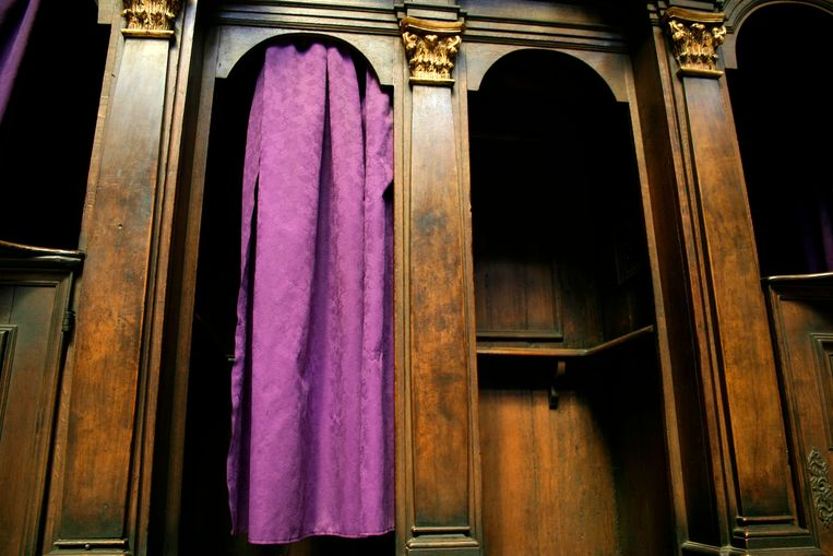 Empty confession booth with violet curtains at St. Vitus Cathedral in Prague, Czech Republic.