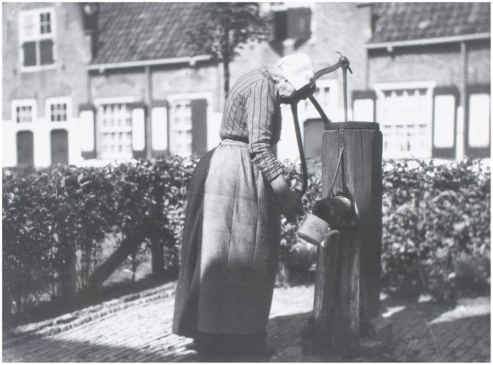 Een vrouw gebruikt de dorpspomp.