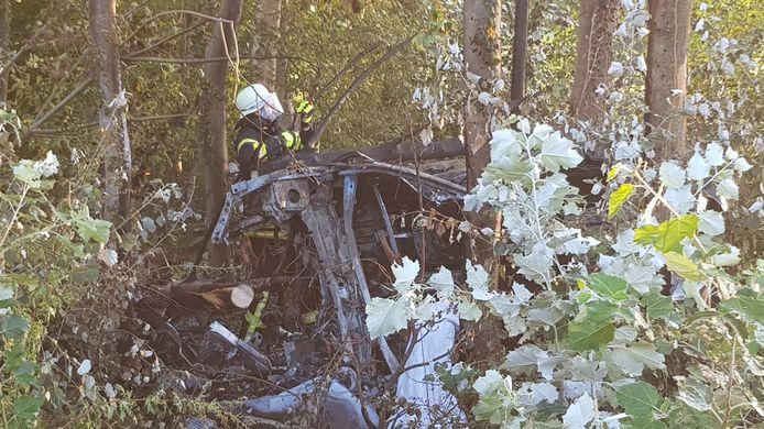Een brandweerman doet onderzoek bij het uitgebrande voertuig langs de A57.