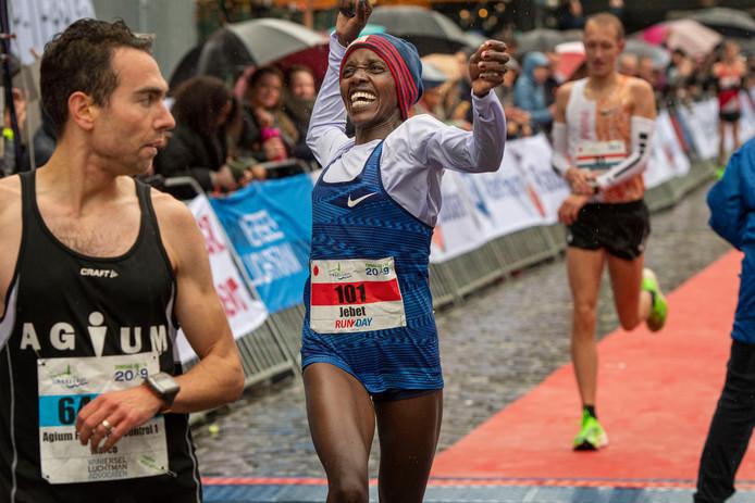 Chaotische aankomst van de winnaar bij de dames. Naom Jebet sligert tussen de mannen door en loopt een pr op de halve marathon tijdens deze kletsnatte singelloop in Breda.