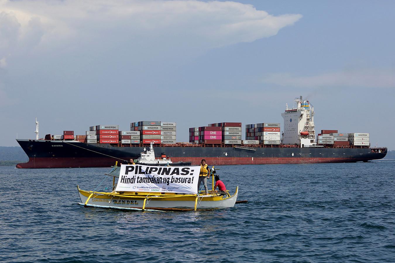 Milieu-activisten van Greenpeace varen rond in de haven van Subic Bay met een spandoek waarop staat 'Filipijnen: geen afvaldumpgebied!'.