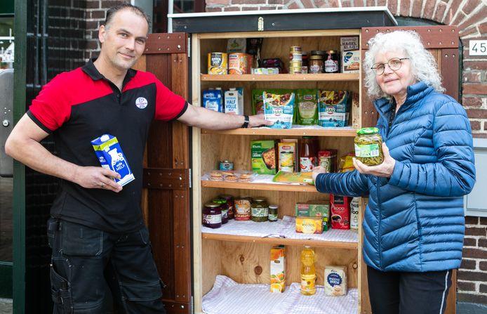 Initiatiefneemster Ria van Steenbruggen en Richard van Dijk, beheerder van De Boerderij, staan bij de hagelnieuwe Voedselkast.
