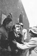 Riet Hoogland wordt opgehaald en feestelijk ontvangen voor het poortje van het Oranjehotel, 16 juni 1941. Riet Hoogland (midden) in Scheveningen.