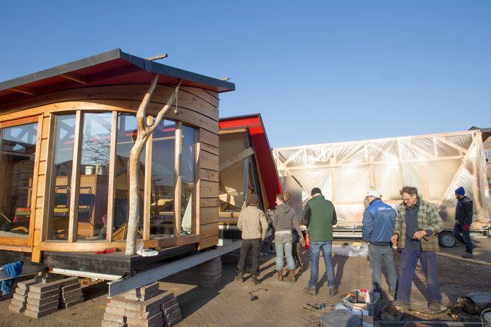 Eindhoven - Houten huis op NRE-terrein moet weg ivm nieuwbouw. Rechtsvoor in geblokte jas Tom van Duuren, eigenaar/initiatiefnemer. Achterin de woonkamer die op een aanhanger is geschoven. Links een van de in totaal 8 units. Hij gaat verhuizen naar Vredeoord.