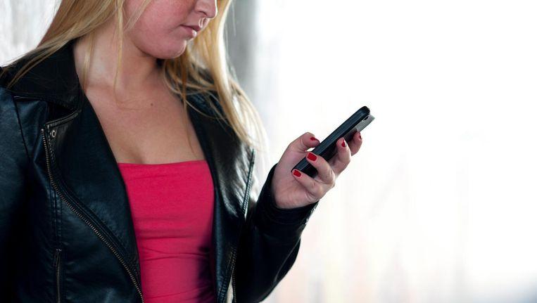 Een meisje bekijkt berichten op haar smartphone. Beeld anp