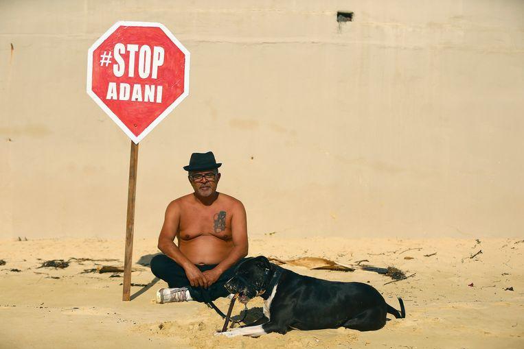 Een strandganger in Sydney demonstreert tegen de beoogde Carmichael-kolenmijn.  Beeld EPA