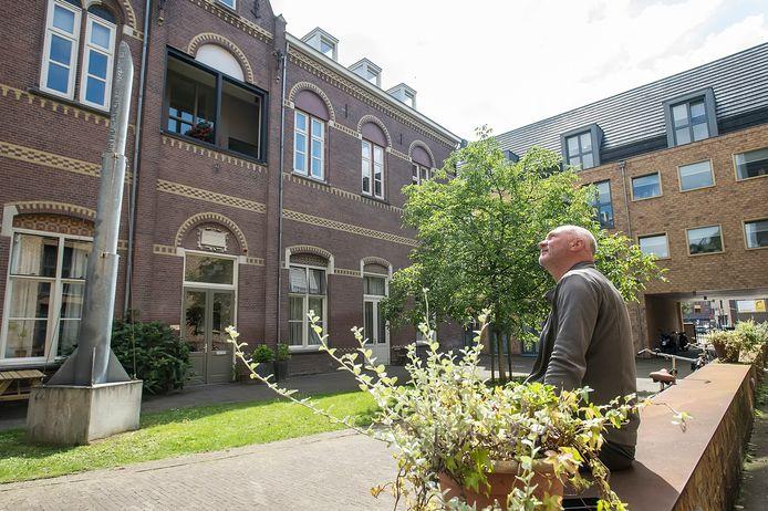 Architect Lukas Ruijs in het door hem opgeknapte Hof van Hersbeek in het centrum van Breda. Links het kunstwerk van Eloi Koreman. In het complex naast de Sint Antoniuskerk wonen mensen zowel begeleid als zelfstandig.