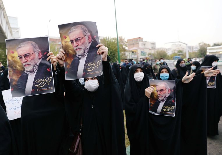 Demonstranten in Iran dragen foto's mee van de vermoordde atoomgeleerde Mohsen Fakhrizadeh in een protest tegen de aanslag.  Beeld Reuters