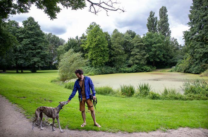 Een man laat zijn hond uit in natuur- en recreatiepark de Blauwe Bergen