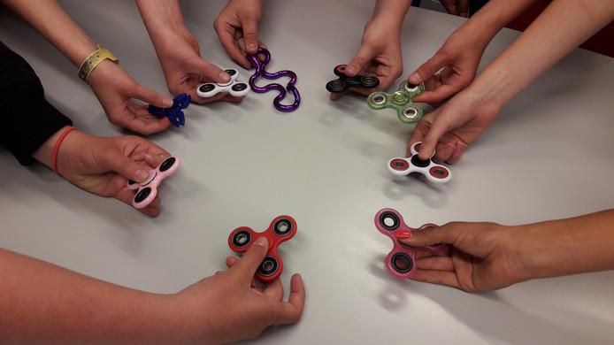 Fidget Spinners in handen van leerlingen van het AOC Oost in Enschede. In het middel een Tangle.
